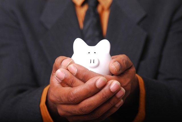 Muž drží v ruce prasátko (pokladničku)